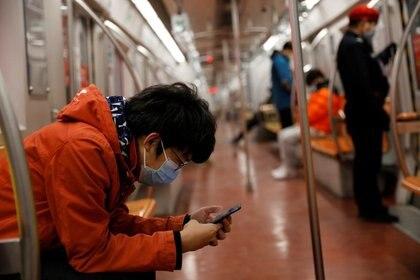 Un hombre con mascariila revisa su teléfono móvil mientras viaja en metro por la mañana después del prolongado día festivo del Año Nuevo Lunar causado por el novedoso brote de coronavirus, en Pekín, China, el 10 de febrero de 2020.  REUTERS/Carlos Garcia Rawlins