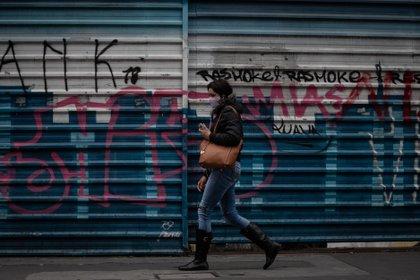 Una mujer camina frente a locales comerciales cerrados en Sao Paulo (Brasil). EFE/ Fernando Bizerra/Archivo