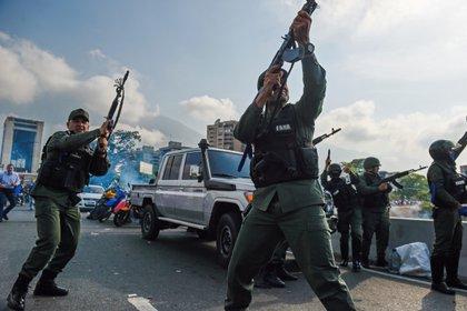 Miembros de la Guardia Nacional que se sumaron al levantamiento disparan al aire a modo de disuasión(Photo by Federico PARRA / AFP)