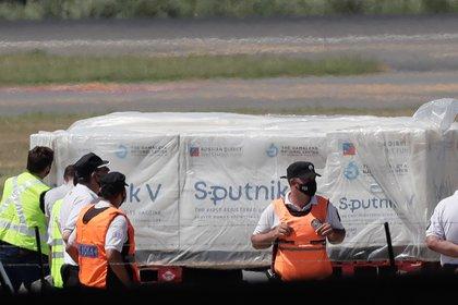 Operarios descargan, el 24 de diciembre de 2020, de un avión de Aerolíneas Argentinas los primeros contenedores de la vacuna rusa Sputnik V contra la covid-19, en el Aeropuerto de Ezeiza (EFE)