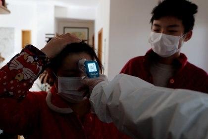 Un trabajador de la saluda controla la temperatura de una mujer en Wuhan (China Daily via REUTERS)