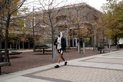 Un estudiante con una máscara protectora camina en el campus de la University of Wisconsin-Madison (Reuters)