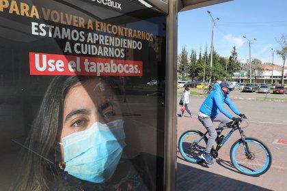 Un hombre circula en bicicleta junto a un anuncio que fomenta el uso del tapabocas, en Bogotá (Colombia). EFE/ Carlos Ortega/Archivo