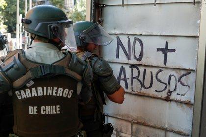 """Miembros de las fuerzas de seguridad miran una pared pintada que dice """"No más abusos"""" durante una protesta (REUTERS/Jorge Silva)"""