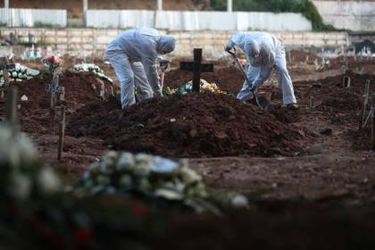 Gravediggers wearing protective garments work as relatives of Neide Rodrigues, 71, who died of the coronavirus disease (COVID-19), attend her burial at a cemetery in Rio de Janeiro, Brazil, May 8, 2020. Picture taken May 8. REUTERS/Pilar Olivares     TPX IMAGES OF THE DAY
