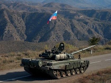 Un miembro de las fuerzas de paz enviadas por Rusia junto a un tanque cerca de la frontera con Armenia el 10 de noviembre de 2020 (REUTERS / Francesco Brembati)