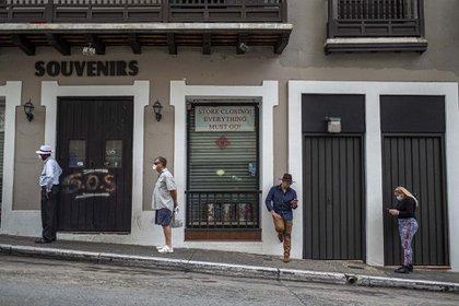 Personas se alinean a una distancia social prudente para ingresar a un supermercado que solo permite a cinco clientes a la vez en San Juan, Puerto Rico como consecuencia de la pandemia por coronavirus (AFP)
