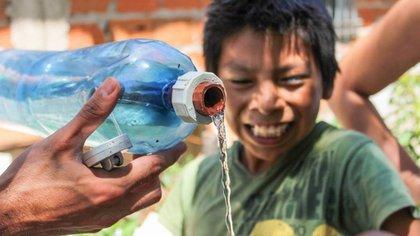 Un niño sonríe ante una de las botellas de agua de la iniciativa Plug-in Social