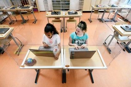 Alumnos sentados detrás de tabiques de plexiglás asisten a una clase en una escuela primaria en Den Bosch, Países Bajos, 8 de mayo de 2020. (REUTERS / Piroschka van de Wouw /archivo)