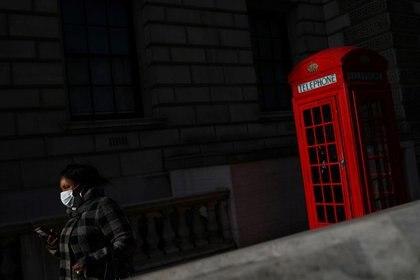 Una mujer con una mascarilla pasa junto a una cabina telefónica en Westminster durante el brote de la enfermedad del nuevo coronavirus (COVID-19), en Londres, Reino Unido, el 11 de mayo de 2020. REUTERS/Hannah Mckay
