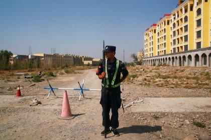 Un policía chino toma su posición en la carretera cerca de lo que oficialmente se llama un centro de formación profesional en Yining en la Región Autónoma Uigur de Xinjiang, China, el 4 de septiembre de 2018 (REUTERS/Thomas Peter/Archivo)