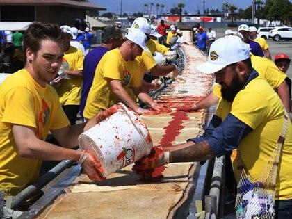 Voluntarios esparcen salsa de tomate y queso en la base de la pizza mientras rompen con éxito el premio Guinness World Records para la pizza más larga con una longitud de 2,13km en la pista del Auto Club Speedway, en Fontana, California el 10 de junio de 2017. Un consorcio de fabricantes de hornos de pizza y panaderos unieron sus fuerzas para romper el récord anterior que ostentaba el Nápoles en Italia por 182 metros. (AFP)