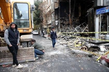 La gente camina cerca de un banco quemado, después de las protestas (Nazanin Tabatabaee/WANA (West Asia News Agency) vía REUTERS)