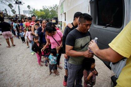 Migrantes se forman para recibir agua embotellada en un campamento de más de 2,000 personas que buscan asilo en EEUU, mientras las autoridades se preparan para responder al brote de coronavirus en Matamoros, México. 22 de marzo de 2020. REUTERS/Daniel Becerril