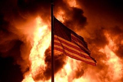 Las llamas envuelven el edificio de la División de Correcciones Comunitarias mientras una bandera estadounidense ondea en un poste (REUTERS/Stephen Maturen)