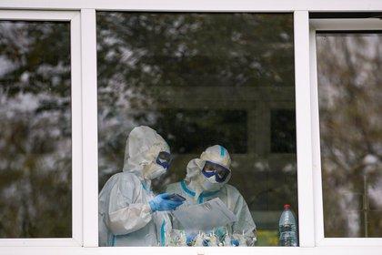 Se ven médicos con trajes protectores en una ventana de un hospital donde se trata a pacientes que padecen la enfermedad del coronavirus (COVID-19)), en Tver, Rusia, el 13 de octubre de 2020 (Reuters/ Tatyana Makeyeva)