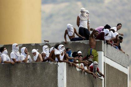 Reclusos se juntan el techo de una prisión en Venezuela durante una revuelta.