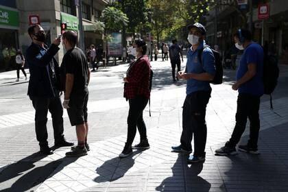 Imagen de archivo de un trabajador bancario tomando la temperatura a clientes afuera de una sucursal en Santiago, Chile, el 3 de abril de 2020. REUTERS/Ivan Alvarado