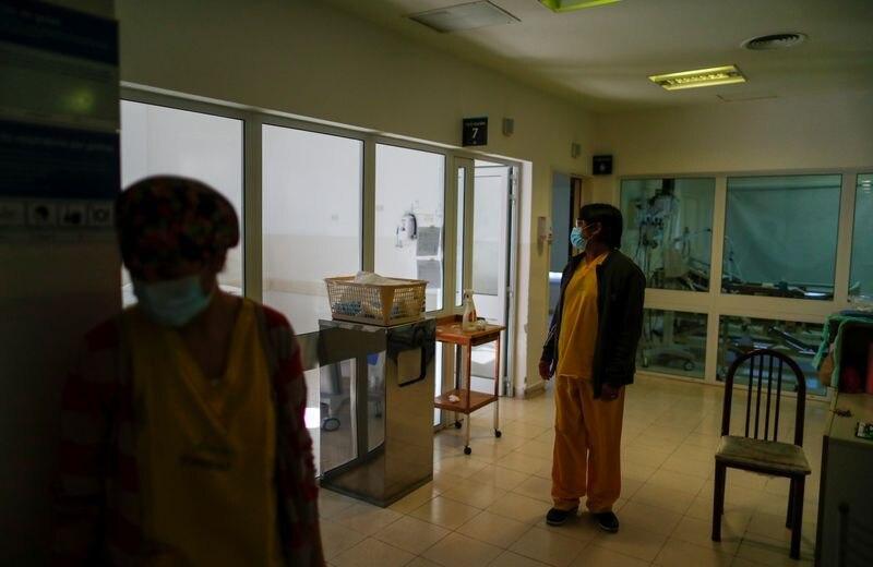 Foto de archivo - Un trabajador de la salud controla a un paciente con enfermedad por coronavirus (COVID-19), en un hospital en las afueras de Buenos Aires, Argentina. La pandemia afecta al mercado financiero nacional. Ago 21, 2020. REUTERS/Agustin Marcarian