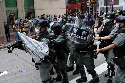 Un paraguas es arrojado contra unos agentes antidisturbios de la policía durante una marcha en contra de los planes de China de imponer una ley de seguridad nacional en Hong Kong (REUTERS/Tyrone Siu)