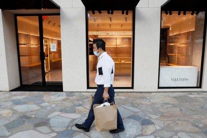 Un hombre camina en frente de una tienda de lujo vacía en Hawaii  REUTERS/Marco Garcia??