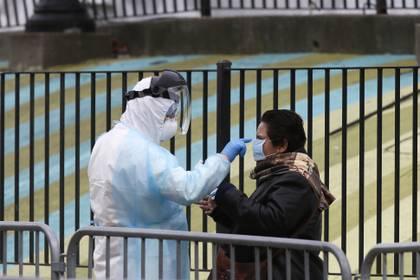 Un trabajador médico distribuye material de protección a personas en fila para hacerse la prueba de coronavirus en el hospital Elmhurst de Nueva York (Reuters/ Stefan Jeremiah)