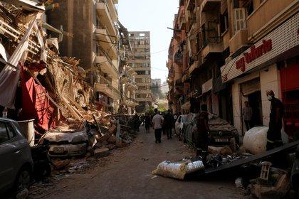 La gente pasa junto a edificios y vehículos dañados tras la explosión del martes en la zona portuaria de Beirut (REUTERS/Carmen Yahchouchi)