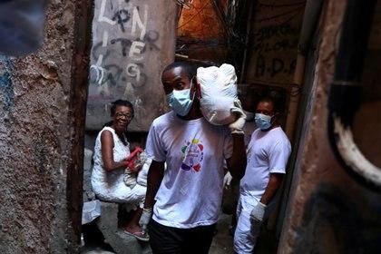 Un voluntario lleva comida a familias pobres de la Rocinha (REUTERS/Pilar Olivares/archivo)