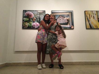 """La autora de """"Aurlia quiere oír"""" junto a sus nietas. Detrás la foto de su casa de la infancia en Galicia. (María Rosa Iglesias)"""