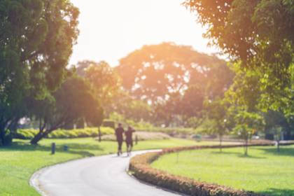 Blurry focus scene of couple walking on the path inside public park with soft orange sunlight in morning.