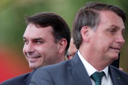 El senador Flavio Bolsonaro sonriente detrás del presidente Jair Bolsonaro (REUTERS/Ueslei Marcelino)