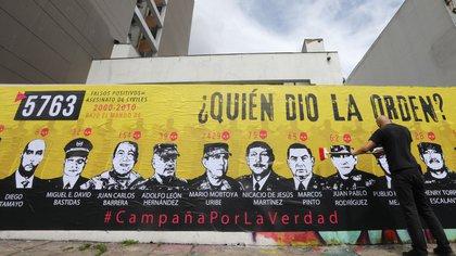 Un hombre participa hoy en la elaboración de un mural sobre los falsos positivos cerca a la JEP, en Bogotá; (Colombia). EFE/ Carlos Ortega