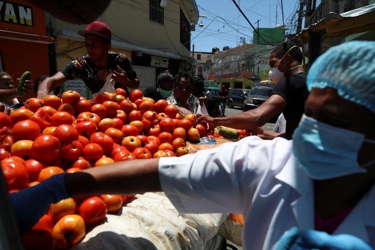 La gente recoge productos descartados de una camioneta debido a que menos gente está comprando en el mercado, en Santo Domingo, República Dominicana, el 15 de abril de 2020. (REUTERS/Ricardo Rojas)