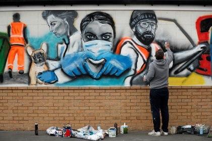 Un artista termina su obra en homenaje a los trabajadores de la salud pública en el Marske Cricket Club del RFeino Unido.