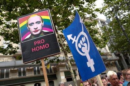 Un participante sostiene una pancarta con una imagen del presidente ruso Vladimir Putin con maquillaje durante el desfile anual del Orgullo en Berlín el 22 de julio de 2017