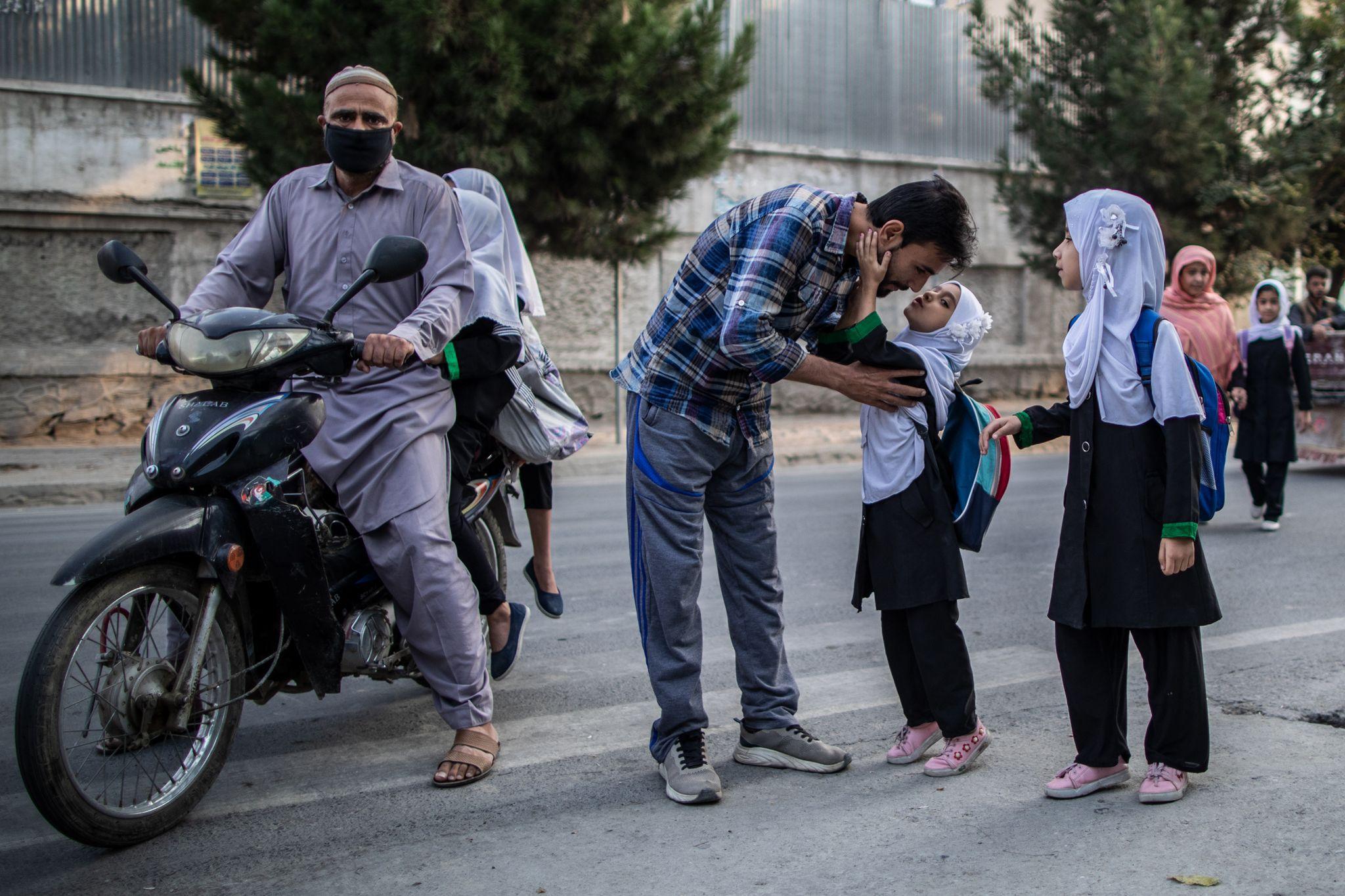 Una niña afgana besa a su padre antes de ingresar a su escuela primaria en Kabul. Foto: Oliver Weiken/dpa