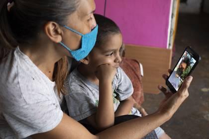 En esta imagen del 27 de abril de 2020, Daniel se sienta en el regazo de su madre en su departamento de Caracas, Venezuela, durante una videollamada con su padre, Misael Cocho. Cocho emigró a Perú y empezó a enviar dinero a su madre y a su hijo con trabajos esporádicos, pero en cuanto consiguió un empleo más estable, los casos del nuevo coronavirus se dispararon. Perdió su empleo. (AP Foto/Ariana Cubillos)