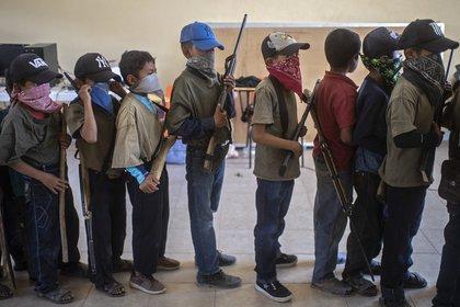 Con palos de madera y armas ficticias, los niños se preparan para el desfile.