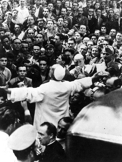 Hombres, mujeres y soldados se reúnen alrededor del Papa Pío XII, con los brazos extendidos, el 15 de octubre de 1943, durante su gira de inspección de Roma, Italia, después de un ataque aéreo estadounidense del 13 de agosto en la Segunda Guerra Mundial. (Foto por AP Photo) (Shutterstock)
