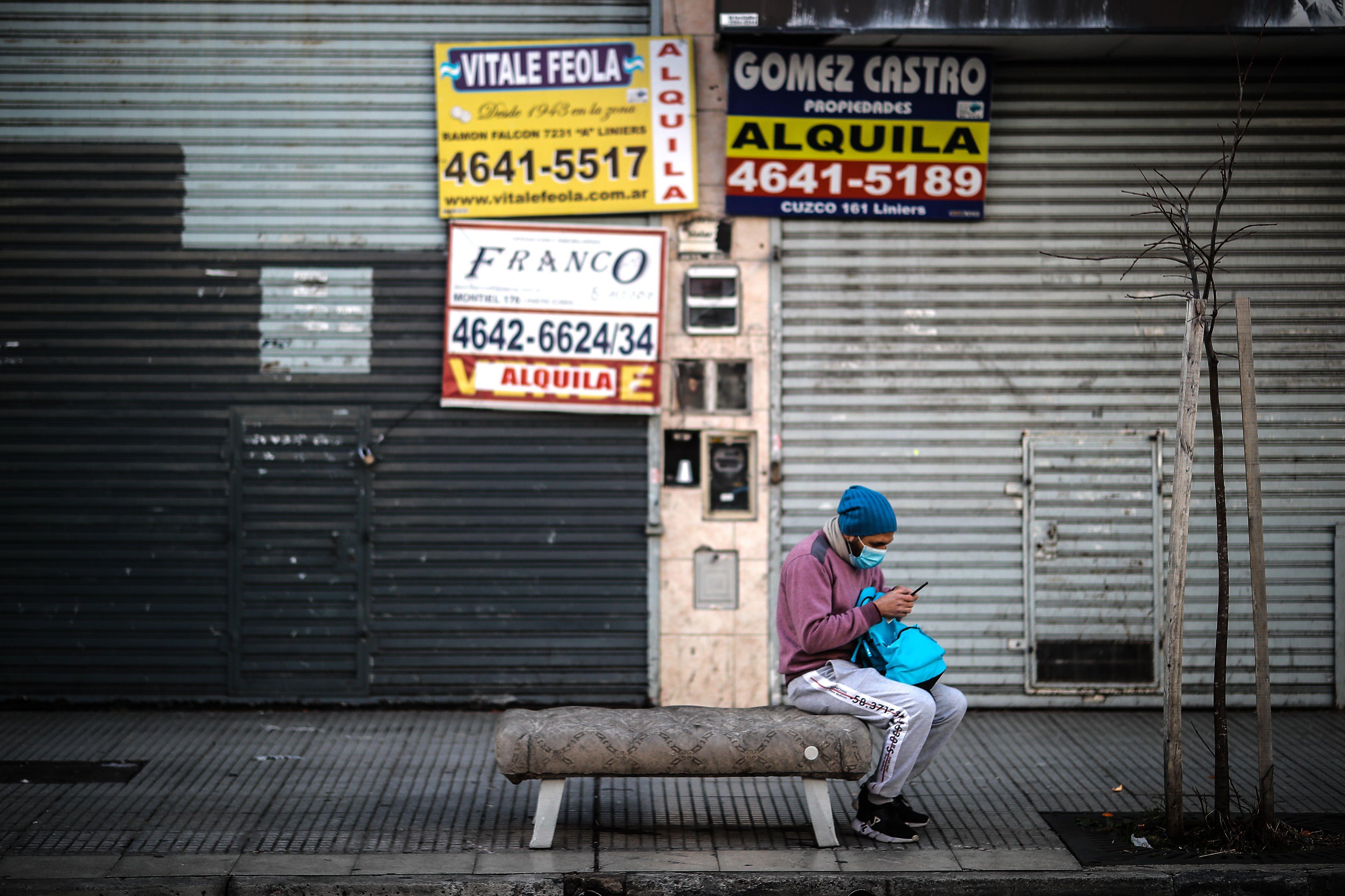 Un hombre revisa su celular frente a locales comerciales cerrados en Buenos Aires (Argentina). EFE/ Juan Ignacio Roncoroni