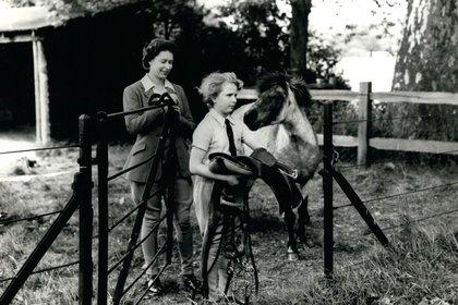 La Reina mantiene la puerta abierta mientras la princesa Ana conduce a su pony Guillermo preparándose para una lección de equitación, 1938