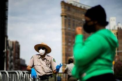 Un guardabosques urbano habla con gente después de quedarse sin máscaras durante una distribución gratuita en la Plaza del Gran Ejército, durante el brote de la enfermedad coronavirus (COVID-19) en el barrio de Brooklyn de la ciudad de Nueva York. 3 de mayo de 2020. REUTERS/Eduardo Muñoz