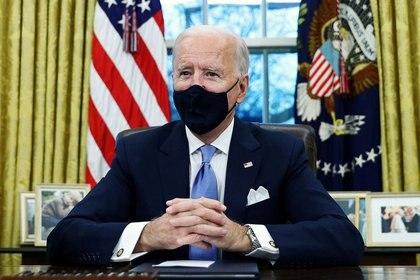 El presidente de Estados Unidos, Joe Biden, firma órdenes ejecutivas en el Despacho Oval de la Casa Blanca en Washington, en su primer día en el cargo, el 20 de enero de 2021. REUTERS/Tom Brenner