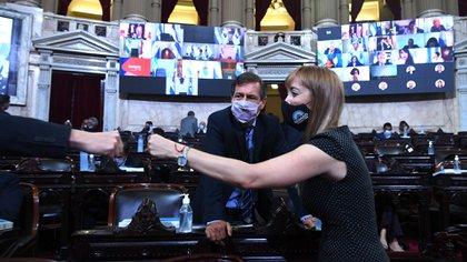 La senadora oficalista por Mendoza, Anabel Fernández Sagasti saluda con el puño a otro legislador. Los observa Luis Naidenoff del interbloque de Juntos por el Cambio. (Comunicación Senado)