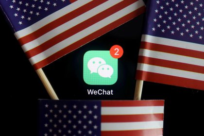 FILE PHOTO: The messenger app WeChat is seen among U.S. flags in this illustration picture taken Aug. 7, 2020. REUTERS/Florence Lo/Illustration/File Photo