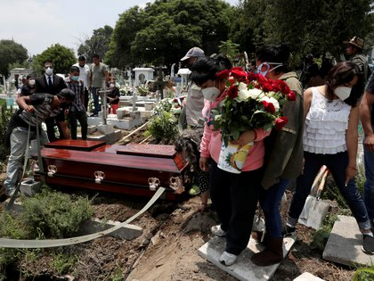 Relatives and friends react near the coffin of a man, during his funeral at the local cemetery, as the coronavirus disease (COVID-19) outbreak continues in Mexico City, Mexico, August 6, 2020. REUTERS/Henry Romero