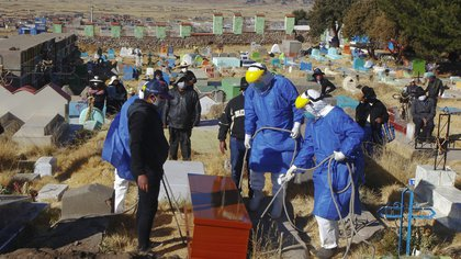 Funerary employees in protective suits prepare to lower the coffin into the ground during the burial of a COVID-19 victim at the local cemetery in the remote Aymara highland village of Acora, one hour away from the city of Puno, close to the border with Bolivia, on August 9, 2020. - Peru registered a new daily record of deaths from the novel coronavirus on August 9, with 228 deaths, surpassing 21,000, amid a vigorous rebound of infections five weeks after the end of a long national confinement. The country, with 33 million inhabitants, is the third country in Latin America in deaths and infections, behind Brazil and Mexico. (Photo by Carlos MAMANI / AFP)