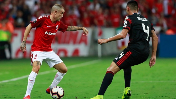 Fabrizio Angileri of Argentinaâ??s River Plate, vies for the ball with Argentine Andres Dâ??Alessandro of Brazilâ??s Internacional, during their Copa Libertadores football match at the Beira-rio stadium in Porto Alegre, Brazil, on April 3, 2019. (Photo by Itamar AGUIAR / AFP)