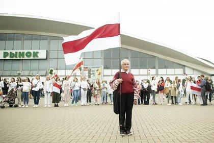 Braginskaya sostiene una antigua bandera de Bielorrusia durante una protesta en Minsk, Bielorrusia, el 22 de agosto de 2020. (Evgeniy Maloletka / AP)