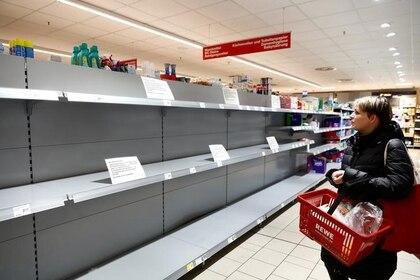 FOTO DE ARCHIVO. Una mujer mira un estante vacío con un letrero que anuncia el racionamiento de papel higiénico a un paquete por persona, en un supermercado de la cadena Rewe, en Potsdam, Alemania. 20 de marzo de 2020. REUTERS/Michele Tantussi.